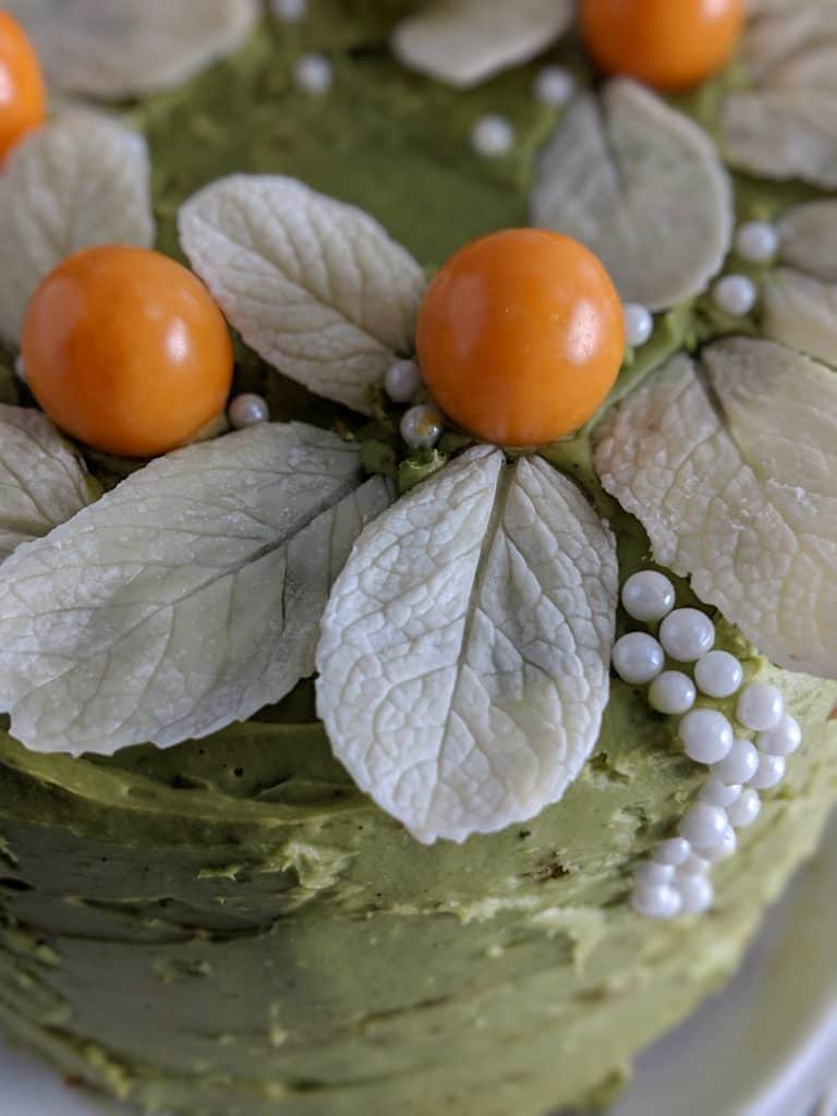 White chocolate leaves with golden berries on a cake with green matcha frosting