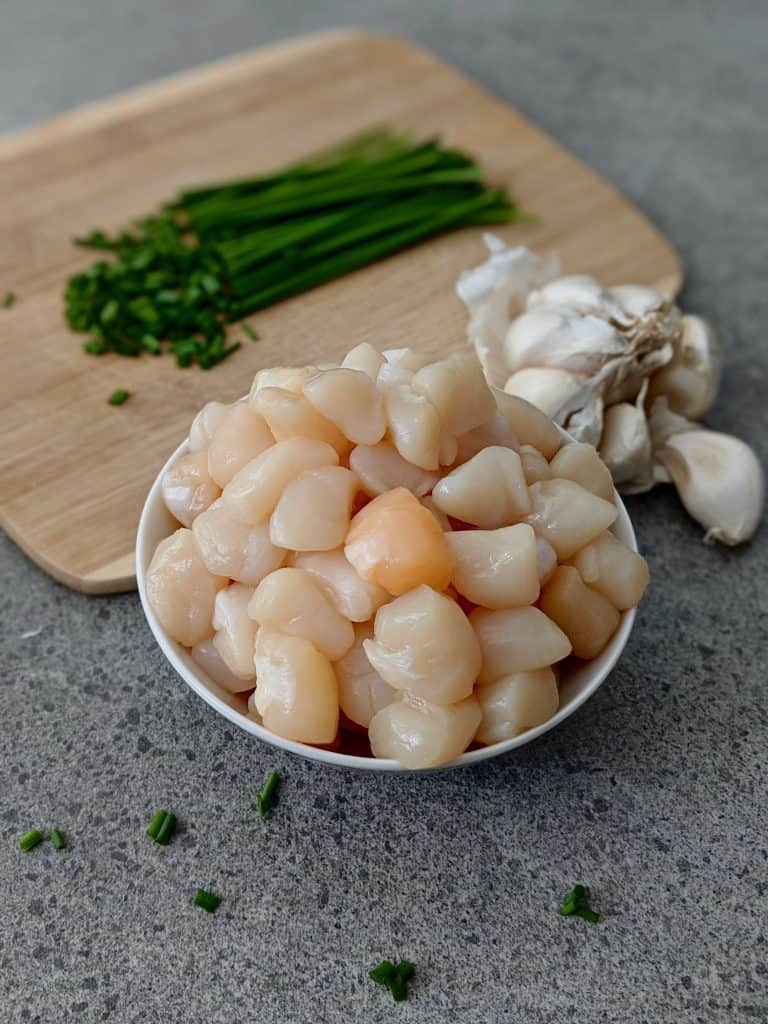 Bay scallops, chives, and a head of garlic on a counter