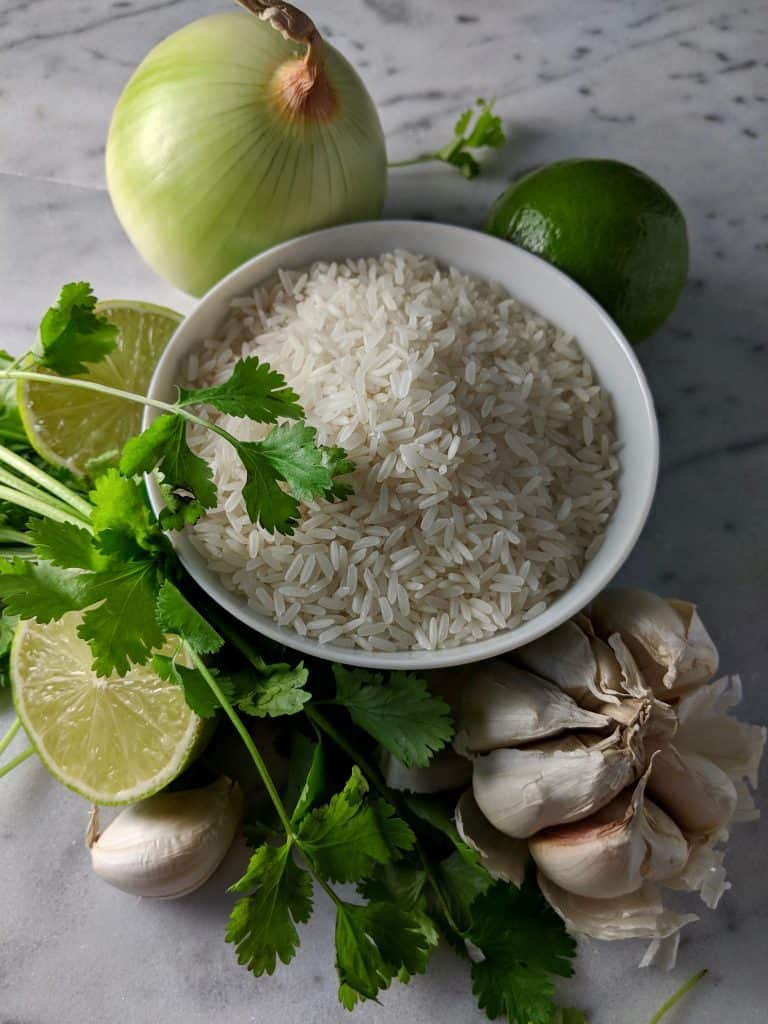 A bowl of jasmine rice with an onion, head of garlic, and limes