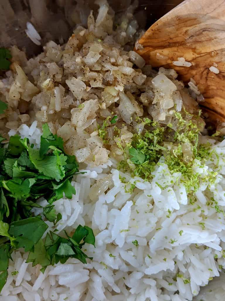 Jasmine rice, cilantro leaves, lime zest, and fried onions in a bowl