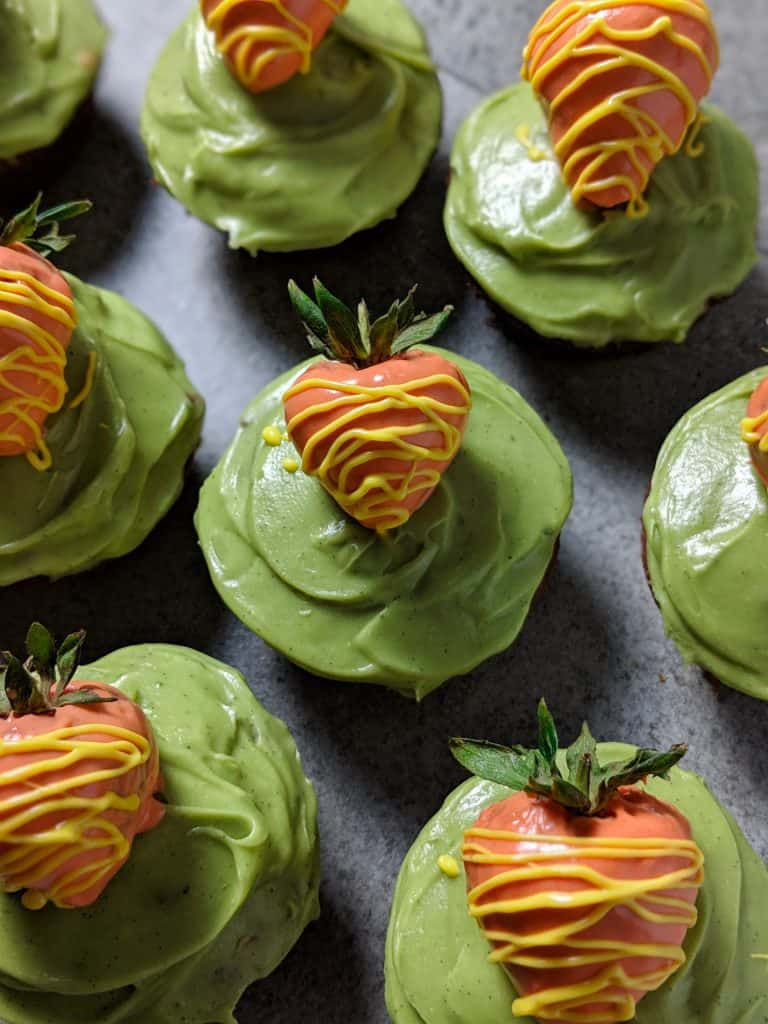 Carrot cake cupcakes with green frosting and strawberry 'carrots'