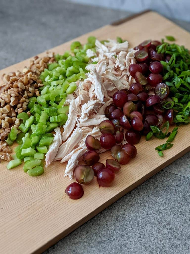 Chop up the ingredients for the chicken & grape salad into small pieces.