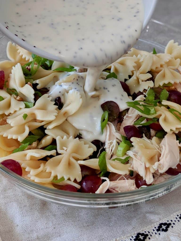 Pour the poppy seed dressing into the bowl with the chicken & grape salad ingredients.