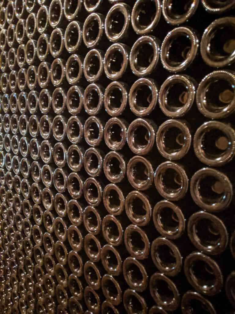 Aging wine bottles stacked in an underground wine cave.