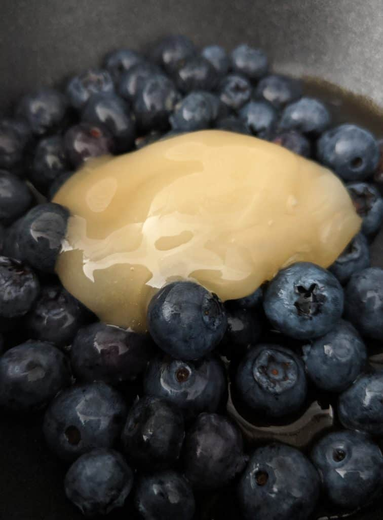 The honey, vanilla extract, water and half of the blueberries are cooked together.