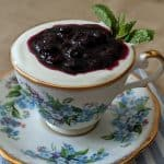 Blueberry vanilla compote on top of yogurt, served in a teacup.