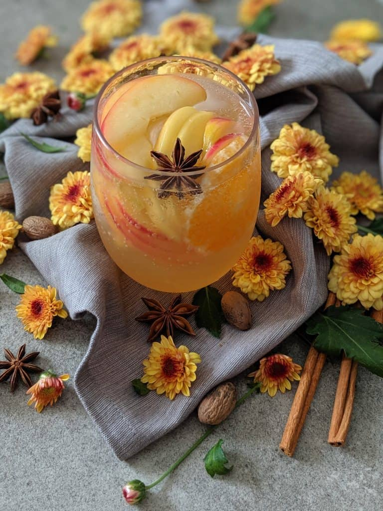 Honeycrisp apple sangria garnished with a star anise pod, surrounded with flowers and spices.