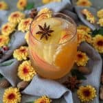 A glass of honeycrisp apple sangria surrounded by flowers and spices.