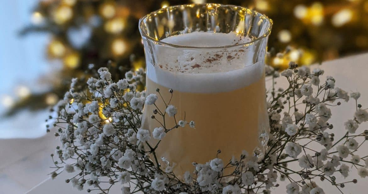 The fresh pear and almond cocktail is served in a glass decorated with baby's breath and rough twine.