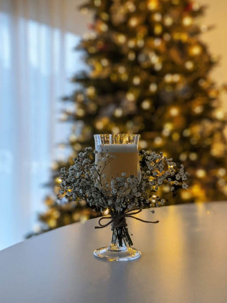 A wide shot of the first snow cocktail with a Christmas tree in the background.