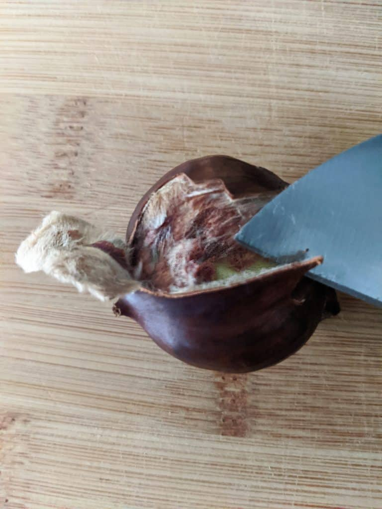 Carefully insert a knife near the base of the chestnut (opposite the pointy end) and peel back the shell.