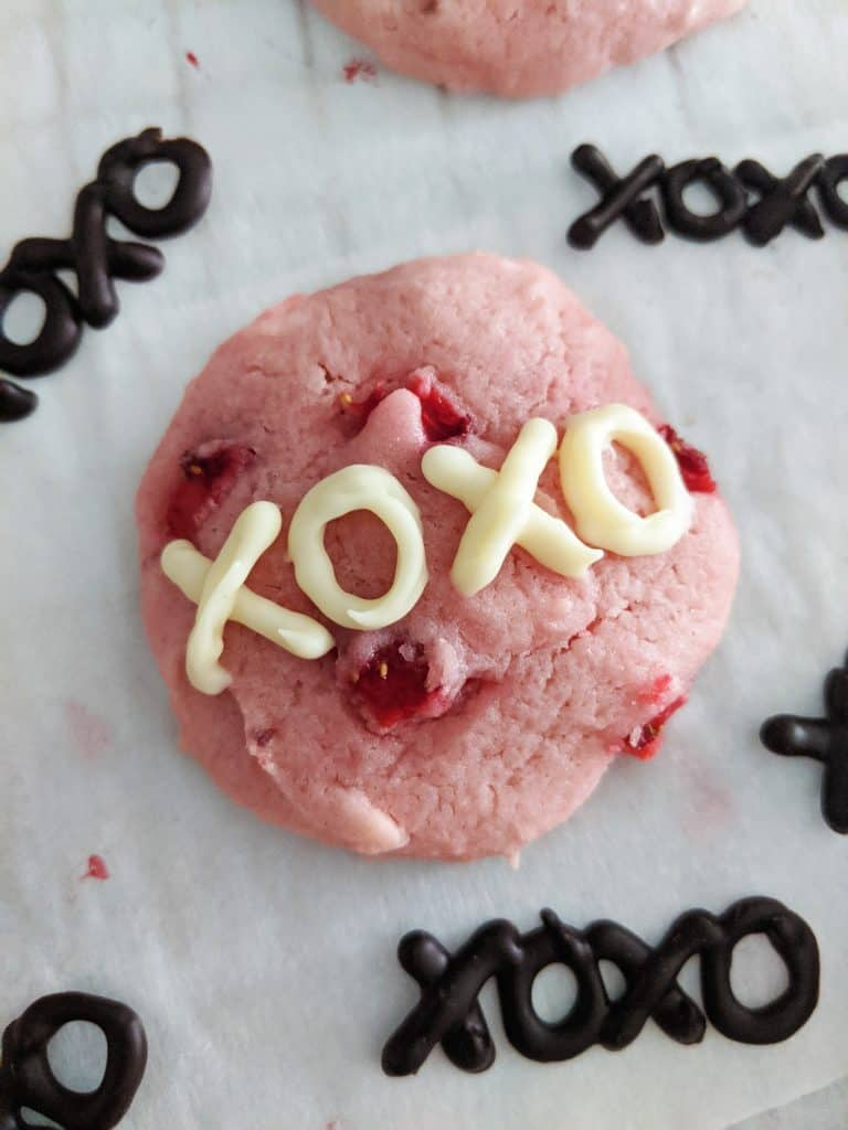 Fresh strawberry cookies decorated with white chocolate writing.