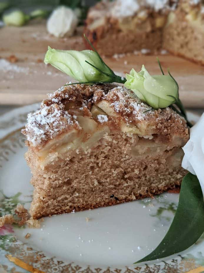A slice of Irish farmhouse apple cake garnished with green flower buds.