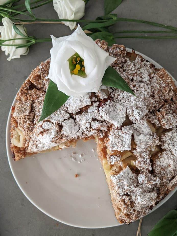 An Irish apple cake dusted with icing sugar, beside white flowers.