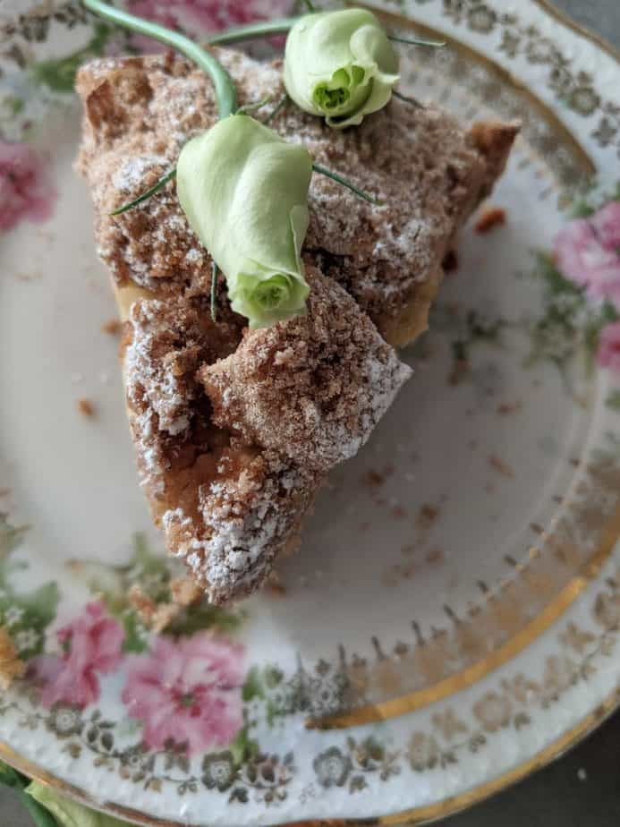 A slice of Irish farmhouse apple cake garnished with green flowers.
