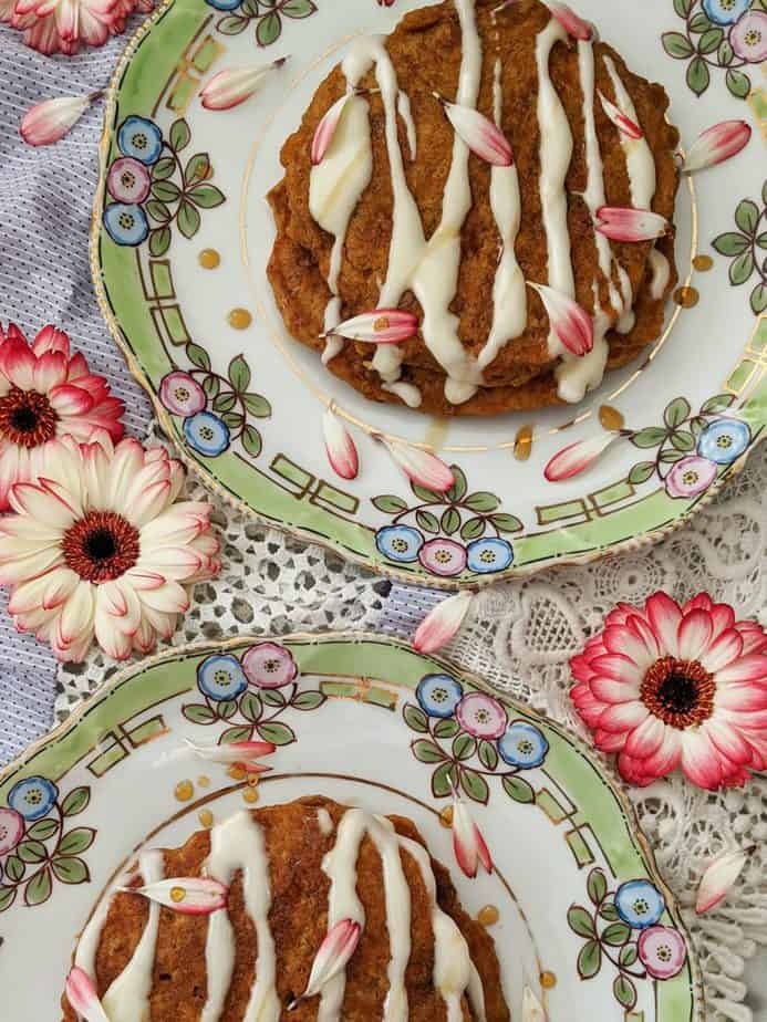 Two plates of carrot cake pancakes surrounded by pink flowers.