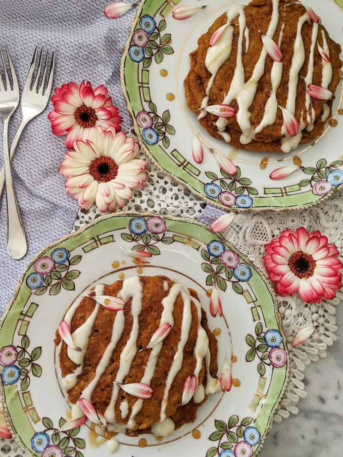 Two plates of carrot cake pancakes drizzled with cream cheese glaze.