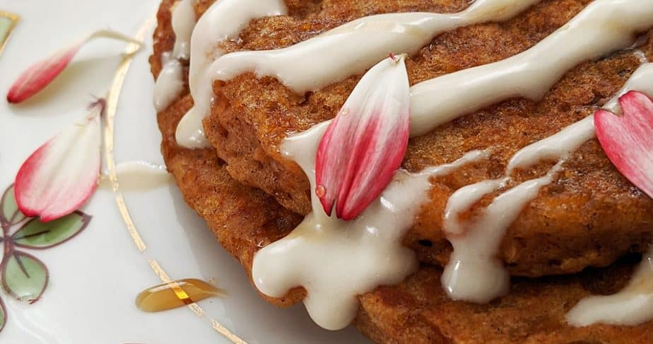 Carrot cake pancakes are drizzled with cream cheese glaze, maple syrup, and edible petals.