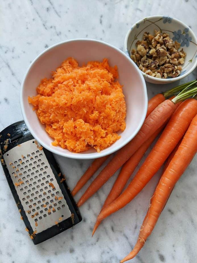 A bowl of finely grated carrots beside a grater and a stack of carrots.