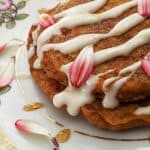 A side shot of carrot cake pancakes with cream cheese glaze, maple syrup, and edible flower petals.