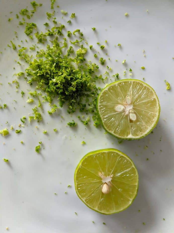 Key lime sliced open beside its zest.