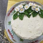 An overhead shot of a lemongrass cake, decorated with icing flowers.