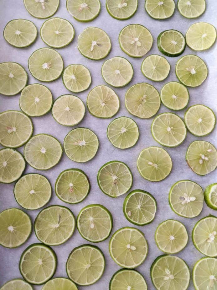 Thinly sliced limes on a parchment paper covered baking sheet.
