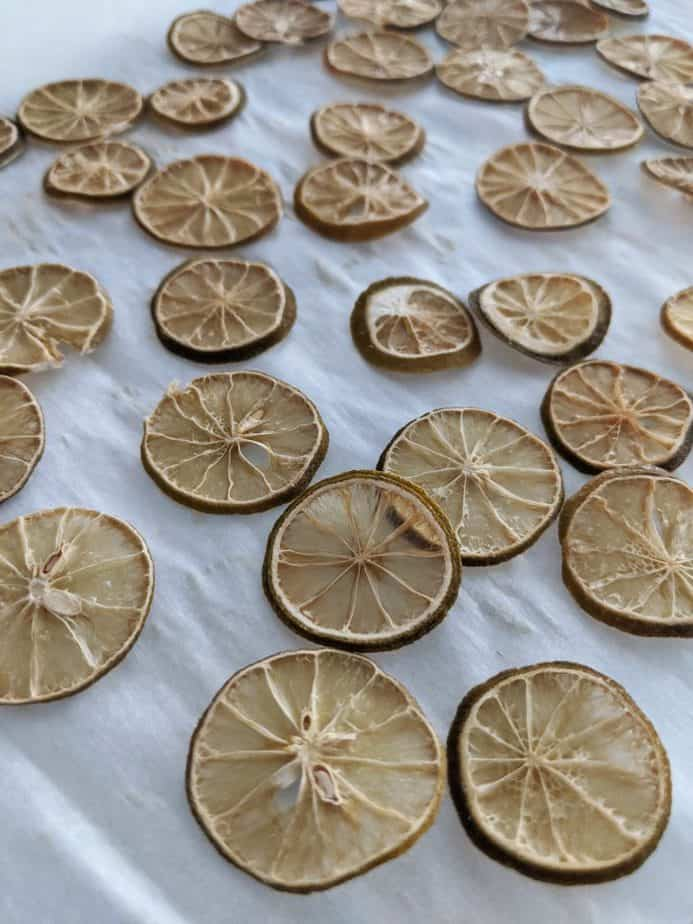 Baked lime slices on a parchment covered baking sheet.