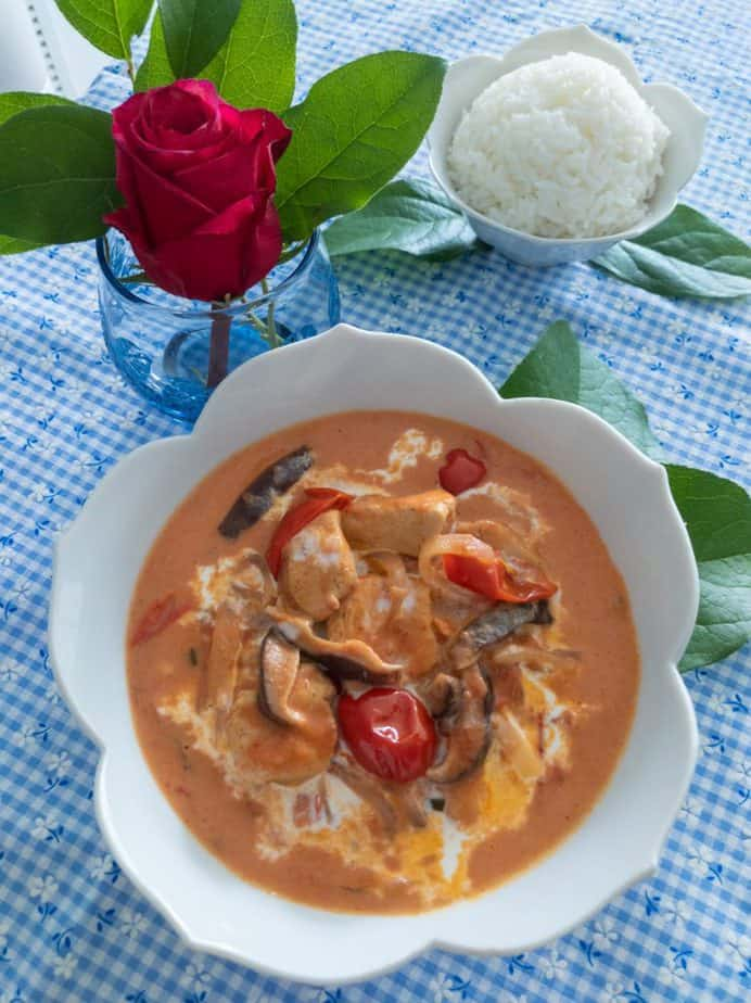 A bowl of Japanese bistro-style creamy tomato chicken in a white bowl on a blue checkered tablecloth.