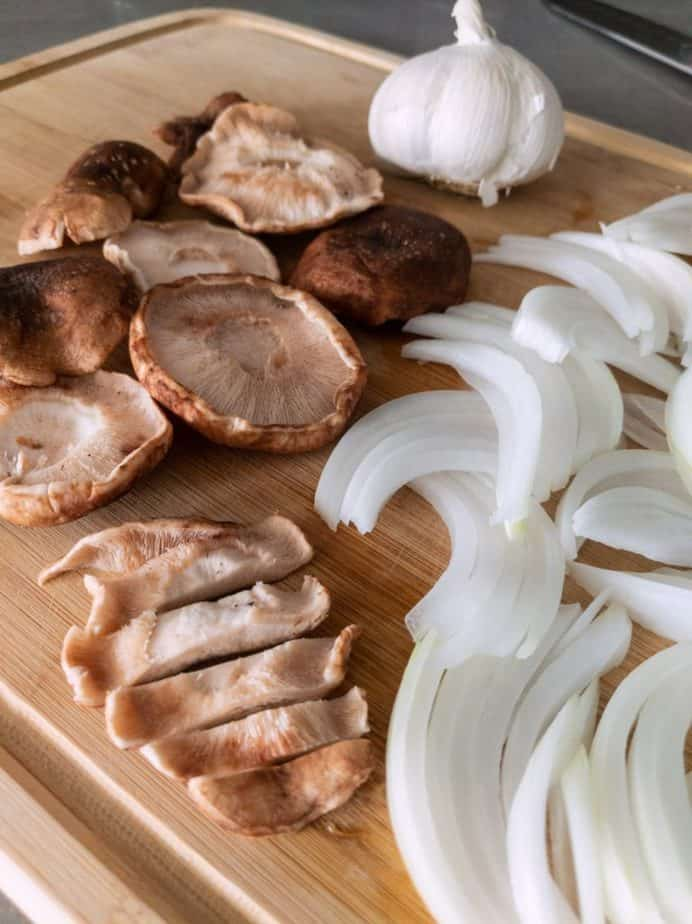Sliced onions and mushrooms on a cutting board.