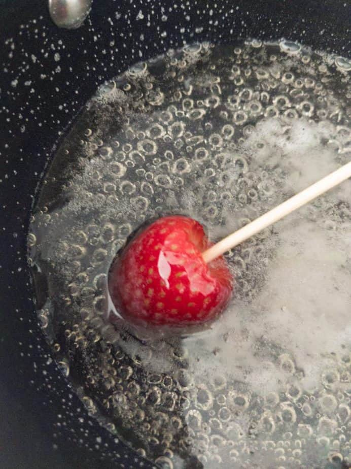 A strawberry being dipped into candy syrup.