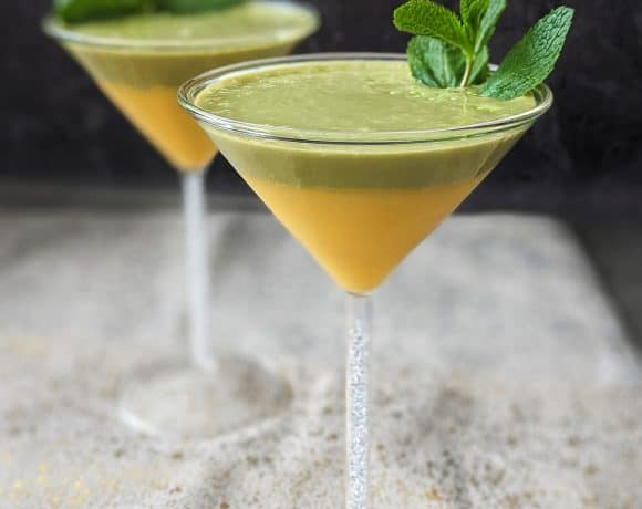 Matcha mango easter smoothies in martini glasses with crystal filled stems.