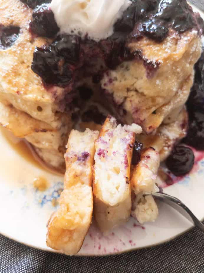 A close up of a fork holding a bite of Mildred's blueberry buttermilk pancakes.