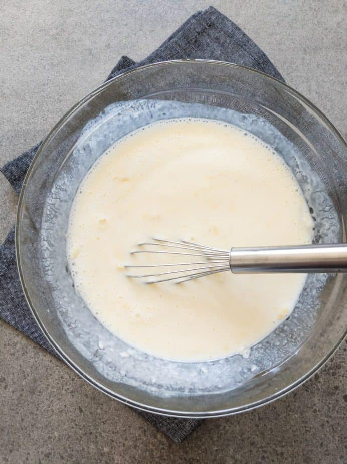 A whisk in a bowl of mixed buttermilk, egg, and melted butter.