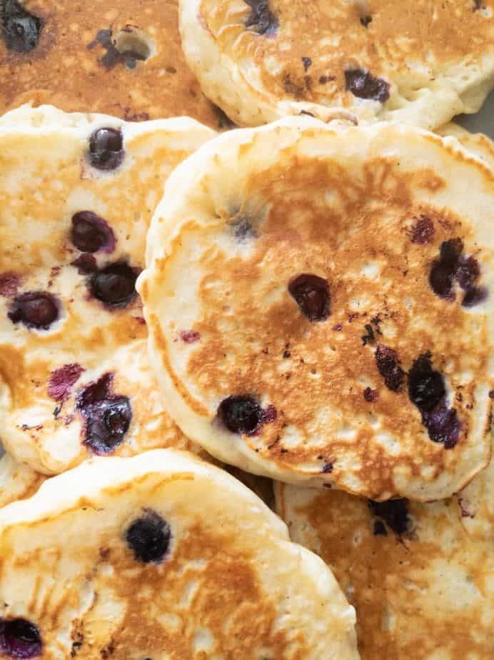 A bunch of Mildred's blueberry buttermilk pancakes stacked together.