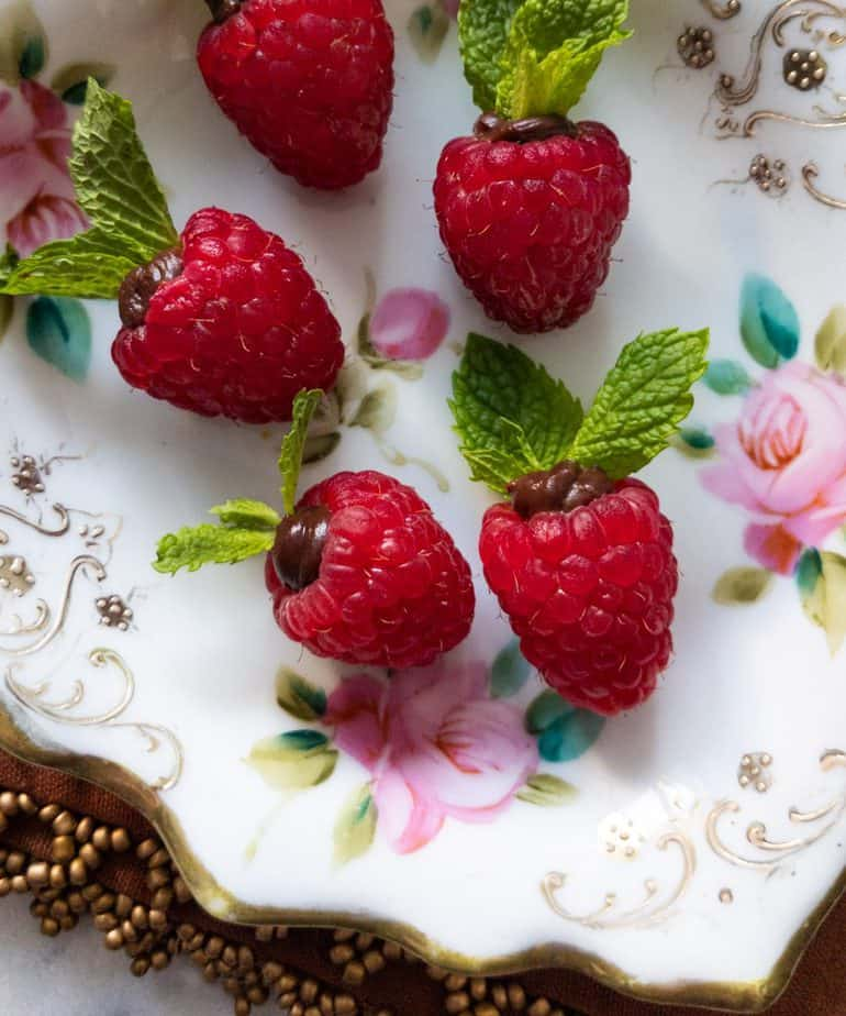 Ganache filled raspberries topped with mint leaves on a rose floral decorated plate.