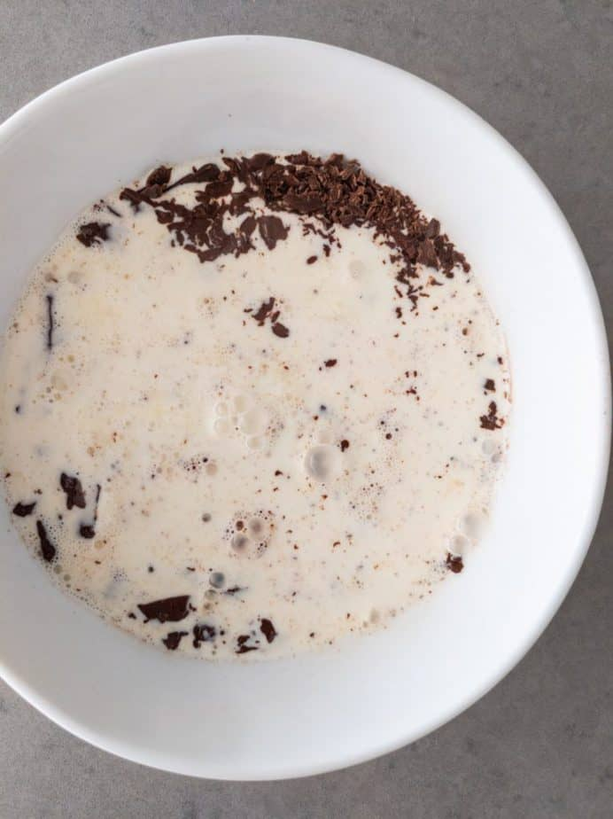 Hot cream on top of finely chopped chocolate in a bowl.