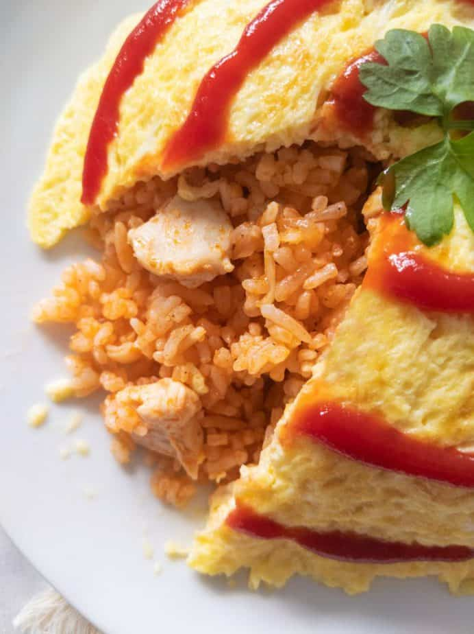 An omurice cut open, revealing chicken rice within.