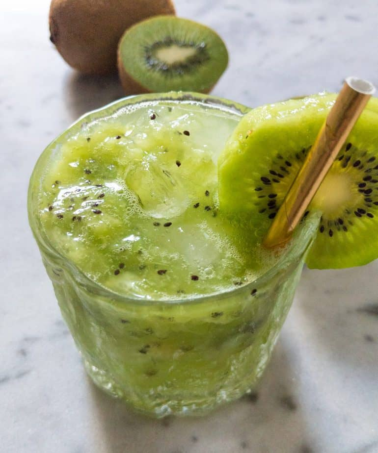 Kiwi kirsch crush in a glass with a slice of kiwi and a golden straw.