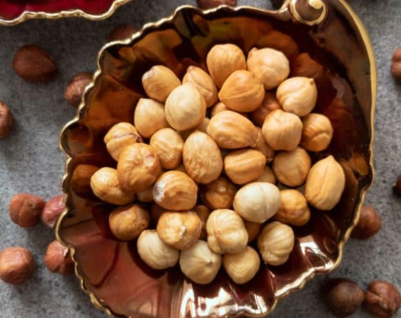Toasted hazelnuts in a brown, leaf-shaped dish.