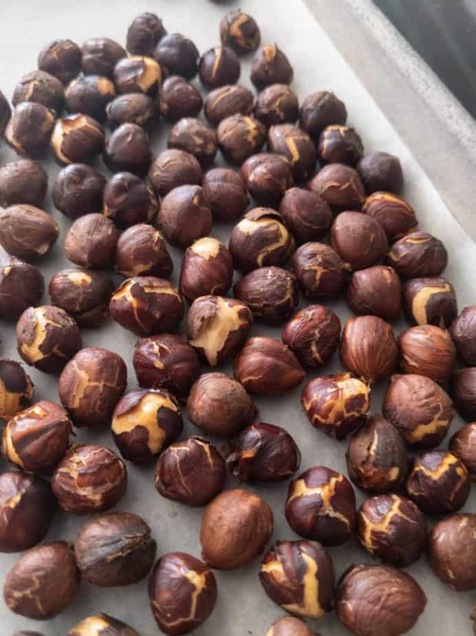 Hazelnuts steaming in their peels on a baking sheet.