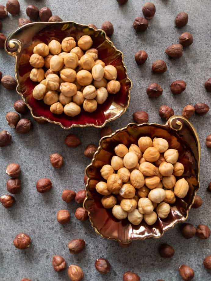 Toasted and peeled hazelnuts in leaf-shaped dishes.