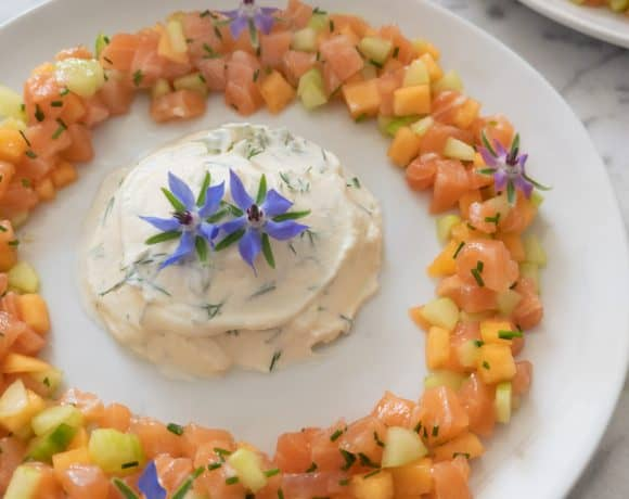 Summer melon salmon tartare with lemon mascarpone, garnished with edible borage flowers.