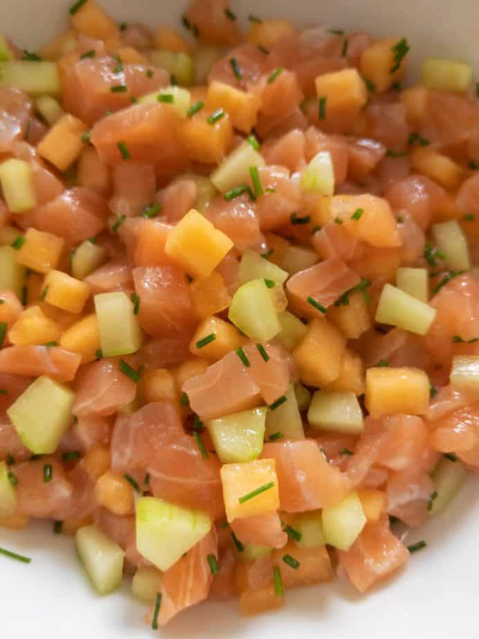 Chopped salmon, melon, cucumber, and chives mixed together in a bowl.