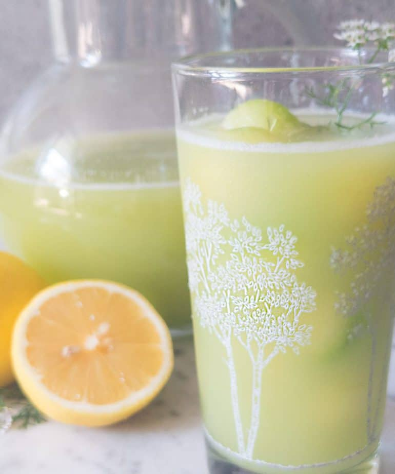 A glass of cucumber lemonade with the pitcher and lemons in the background.