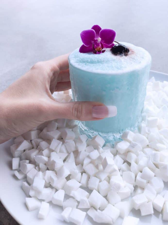 A hand holding up a blue cocktail.