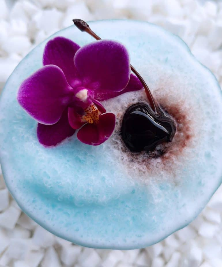 An icy blue coloured blue Hawaiian colada in a glass topped with an orchid and a maraschino cherry.