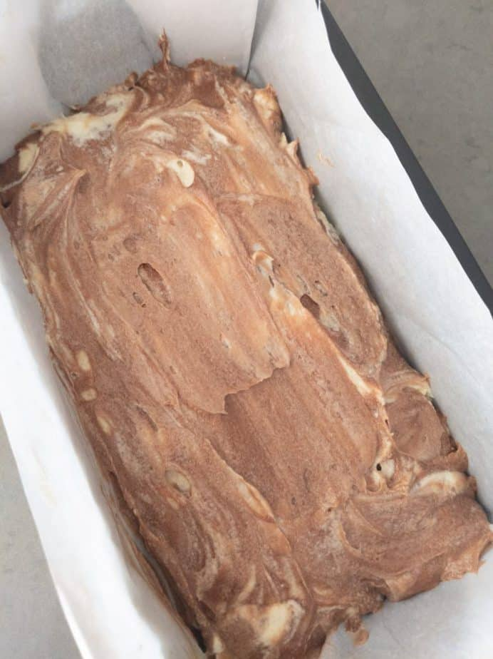 Marble cake batter in a parchment paper lined loaf pan.