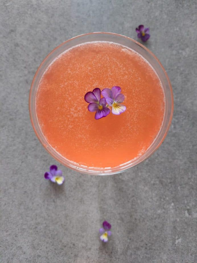 An overhead shot of naked and famous cocktail in a coupe glass garnished with violets.