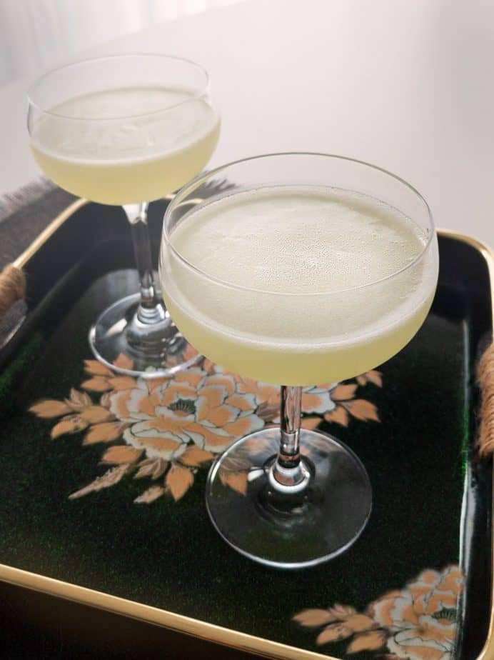 Two last word cocktails sitting on a tray with a floral pattern.